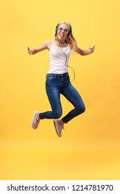 Full-length portrait of carefree woman in jean jumping while listening music. Indoor photo of adorable caucasian female model in white t-shirt fooling around in studio with yellow background.