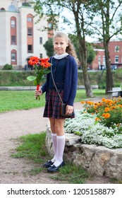 Full-length portrait of Caucasian schoolgirl in uniform going back to school, holding flowers in hands