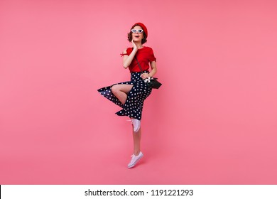 Full-length portrait of cheerful well-dressed girl having fun in studio. Debonair french lady with short brown hair dancing on pink background.