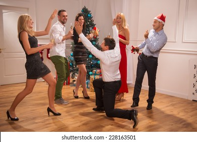 Full-length portrait of the company of happy friends wearing great costumes dancing together near the Christmas tree celebrating New Year drinking champagne one of them standing on his knees back to