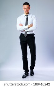 Full-length portrait of confident businessman with arms folded on gray background