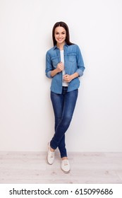 Full-length portrait of cute cheerful smiling young pretty woman  in casual jeans clothes standing near white wall