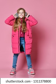 full-length portrait of Cute smiling girl in winter puffer jacket and fur headphones over pink wall background