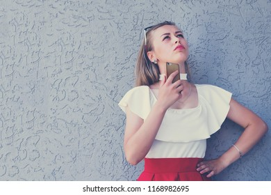 Full-length portrait of cute young female looking up and holding mobile phone. Pensive and fashionably dressed woman posing outdoors. Isolated on grey background with copy space in left side