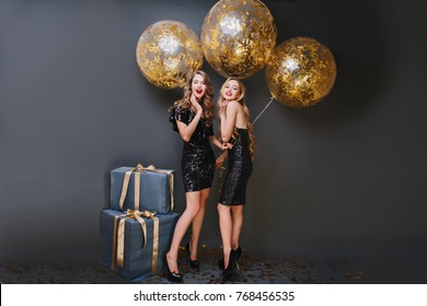 Full-length portrait of dreamy female model with curly hairstyle holding party balloons in her room. Indoor photo of pleased girl wears black dress and standing near blue gift box.
