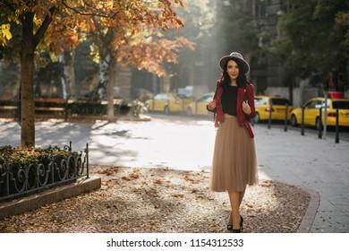 Full-length portrait of enchanting brunette girl standing on the street in sunny day. Outdoor shot of slim pleased lady in long skirt enjoying nature views in autumn.