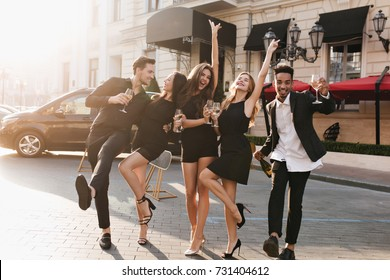 Full-length portrait of fascinating girl in elegant sandals dancing with boyfriend on the street while posing with friends. Outdoor photo of cheerful young people fooling around and drinking champagne