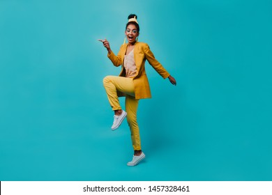 Full-length portrait of fashionable african woman jumping on blue background. Indoor photo of black girl dancing in yellow costume.
