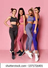 Full-length portrait of four sport girls international friends posing on pink background. Sporty young woman in blue gray brown sport wear happy celebrate smiling