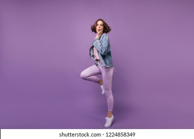 Full-length portrait of funny charming woman dancing in studio. Lovely slim girl in oversize jacket jumping on purple background.