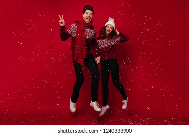 Full-length portrait of funny couple jumping under snow. Indoor photo of pretty girl in scandinavian sweater chilling with boyfriend during christmas holidays.