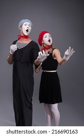 Full-length portrait of funny mime couple with white faces solemnly singing and waving their hands isolated on grey background with copy place