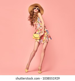 Full-length portrait Gorgeous Fashion Lady in Floral Dress. Trendy wavy Hairstyle. Sexy Young Model, Stylish Sunglasses, fashionable Heels. Playful Summer Girl on Pink