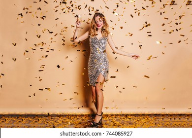 Full-length portrait of graceful fair-haired woman in trendy attire chilling at christmas party. Joyful caucasian female model with curly hair having fun during photoshoot with confetti.