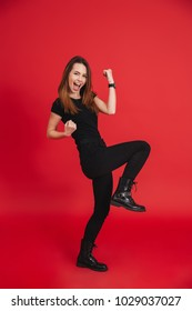 Full-length portrait of happy woman 20s wearing black t-shirt screaming and clenching fists in rejoicing victory or triumph isolated over red background