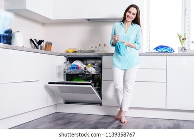 Full-length portrait of a happy young housewife in white jeans and a turquoise shirt in a white kitchen standing with a towel in her hands next to an open dishwasher, modern cleaning, washing dishes
