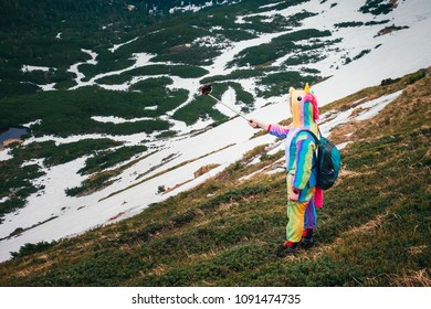 Full-length portrait of a hiker in unicorn costume taking selfie on mobile phone in wild nature of Carpathians surrounded with green grass and snow leftovers.High angle view.Wanderlust travel concept.