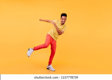 Full-length portrait of joyful african male model dancing in yellow shoes. Cheerful black man enjoying photoshoot on bright background.
