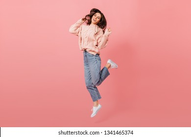 Full-length portrait of jumping dark-haired girl. Lady in jeans and pink sweater having fun on isolated background