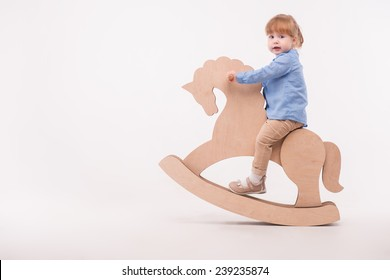 Full-length portrait of little lovely smiling girl wearing blue shirt and brown pants swaying on the wooden toy horse. Isolated on the white background