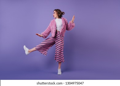 Full-length portrait of lovable curly woman dancing in striped pants. Studio shot of fashionable brunette girl jumping on purple background.
