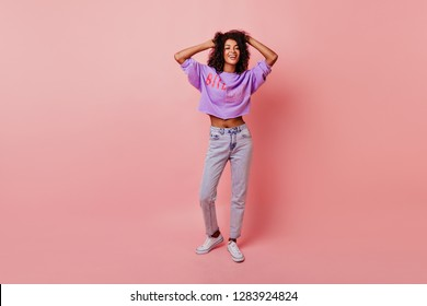 Full-length portrait of lovely slim woman touching her soft black hair. Blithesome african girl in jeans dancing on rosy background.