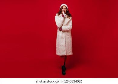 Full-length portrait of magnificent ginger woman standing on red background. Refined female model in coat enjoying winter photoshoot.