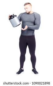 Full-length portrait of male fitness instructor holding container with sports nutrition on white background
