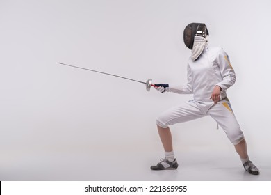 Full-length portrait of nice young woman wearing fencing costume and mask practicing before very important competitions. Isolated on white background