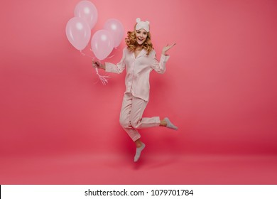 Full-length portrait of pleasant birthday girl in socks jumping on pink background. Cute young woman in pyjamas and sleepmask having fun with helium balloons.