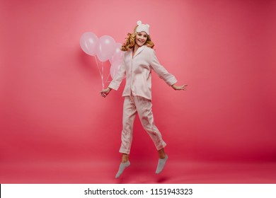 Full-length portrait of pleased fair-haired lady relaxing after party. Indoor photo of positive birthday girl expressing energy on pink background.