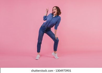 Full-length portrait of pleased white girl in trendy denim pants. Indoor photo of smiling good-humoured woman posing on pink background.