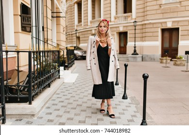 Full-length portrait of pretty woman in vintage dress standing with legs crossed in front of beautiful buildings. Outdoor photo of glamorous blonde girl wearing light-brown coat and trendy shoes.