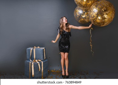 Full-length portrait of refined european girl wears black dress at birthday party. Blissful long-haired lady with balloons can't wait to open presents.