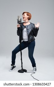 Full-length portrait of rock singer wearing leather jacket and keeping static mic, sings a song loudly on grey background. Concept of rock music and rave