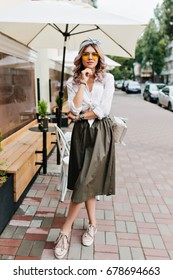 Full-length portrait of romantic girl in midi skirt and white shirt standing in confident pose under summer umbrella. Amazing young lady with curly hair posing with cute backpack in outdoor cafe.