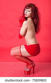 Full-length portrait of sexy young red-haired woman on red background