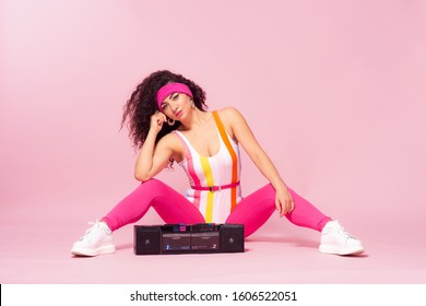 Full-length portrait of slim woman in color bodysuit and pink leggings in style of 80s, doing aerobics. Studio shot of shapely female model in aerobics form holding boombox. Toned photo