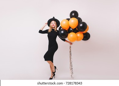 Full-length portrait of slim woman in wizard attire dancing in studio with colorful balloons. Enchanting blonde girl in high heel shoes and witch hat having fun at halloween party.