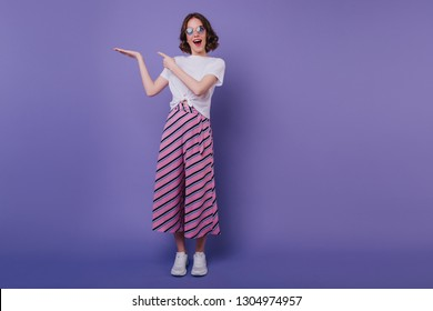 Full-length portrait of spectacular pretty woman in pink striped pants. Indoor shot of amazing good-humoured girl posing on purple background.