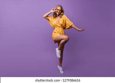Full-length portrait of stunning female model jumping with smile. Studio photo of joyful caucasian woman in orange dress.