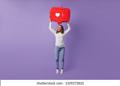 Full-length portrait of stylish female blogger standing on purple background. Dreamy caucasian girl in white sweater dancing in studio.