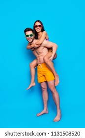Full-length portrait of summer travelers isolated on blue background. Joyful couple, man in eyewear and yellow shorts carrying on back happy woman with dark hair and looking at camera