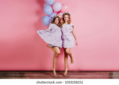Full-length portrait of two barefooted ladies having fun at party. Indoor photo of caucasian girls in dresses dancing with balloons.