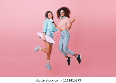 Full-length portrait of two sporty ladies jumping during indoor photoshoot and smiling. Glamorous skater girl in blue shirt having fun with african female friend in black shoes.