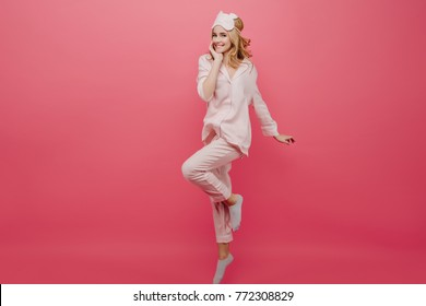 Full-length portrait of winsome girl in pajamas and socks dancing on pink background. Studio shot of graceful caucasian female lady in eyemask having fun in morning.