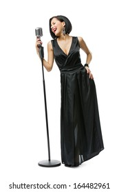 Full-length portrait of woman musician wearing long black evening dress and holding mic