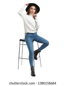 Full-length portrait young brunette woman in blue jeans and white sweater, isolated on white background