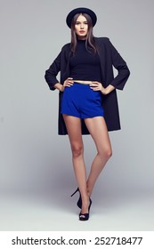Full-length portrait young elegant woman in blue shorts, black jacket and hat. Fashion studio shot