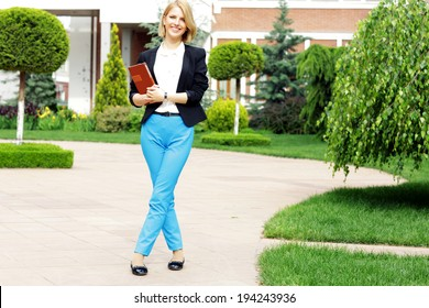 Full-length portrait of a young happy woman in garden